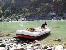 流动的河、小船有人的和山 免版税库存图片