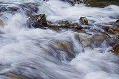 流动的水特写镜头在岩石的 库存照片