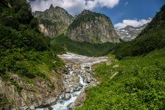 流动从冰川下面的凉快的山小河 高地通行证 免版税库存图片