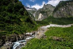 流动从冰川下面的凉快的山小河 高地通行证 图库摄影