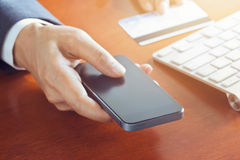 流动付款,使用智能手机和信用卡的商人为网上购物 免版税库存图片