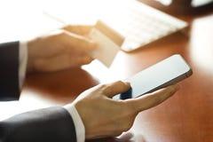 流动付款,使用智能手机和信用卡的商人为网上购物 免版税库存照片