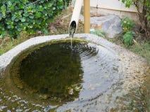 流动从管子的水反对岩石 库存图片