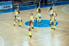 从流动代课教师组的女孩啦啦队欢呼您喜爱的蓝球队。 库存图片