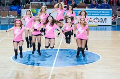 从流动代课教师组的女孩啦啦队欢呼您喜爱的蓝球队。 免版税库存图片