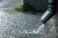 流动从金属水落管的雨水在洪水期间 的概念防护大雨 免版税库存照片