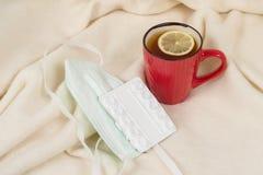 流感季节-茶,医疗面具,药片,背景-有格子花呢披肩的家庭扶手椅子 图库摄影