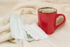 流感季节-茶,医疗面具,药片,背景-有格子花呢披肩的家庭扶手椅子 免版税库存照片