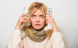 流感家补救 女服温暖的围巾,因为病症或流感 女孩举行玻璃水片剂和温度计光 免版税库存照片