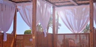 流洒有织品白色帷幕的遮篷在风的海滨微风 免版税库存照片