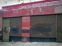 流浪汉有被关闭的被破坏的商店前面的被放弃的商店与剥在都市街道上的红色油漆 免版税库存图片