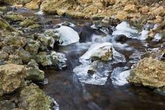流经在一条岩石小河下的被弄脏的水冰 库存图片