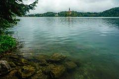 流血与湖、海岛、城堡和山在背景中在有薄雾和雨天, 免版税库存照片