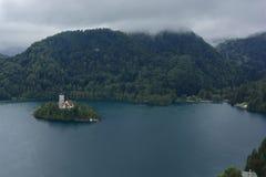 流血与湖、海岛、城堡和山在背景中在有薄雾和雨天 图库摄影