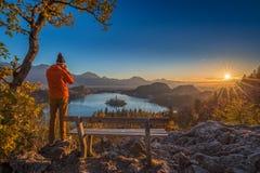 流血,斯洛文尼亚-戴橙色夹克和帽子的摄影师旅客为全景秋天日出照相 免版税库存照片