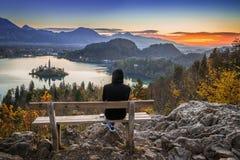 流血,斯洛文尼亚-放松和享受美好的秋天视图和五颜六色的日出的赛跑者妇女 免版税库存图片