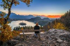 流血,斯洛文尼亚-放松和享受美好的秋天视图和布莱德湖的五颜六色的日出红色头发赛跑者妇女 免版税库存照片