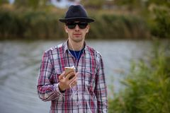 流行的服装的年轻人有电话的和听到音乐 图库摄影