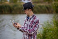 流行的服装的年轻微笑的人听到音乐 免版税图库摄影