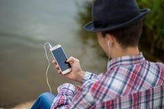 流行的服装的年轻微笑的人听到音乐 库存图片