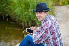 流行的服装的年轻微笑的人听到音乐 免版税库存图片