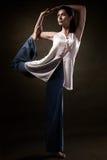 流行的服装的时髦的年轻运动女孩,显示瑜伽asanas在演播室 秀丽面孔和身体健康 图库摄影