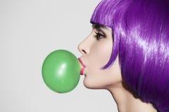 流行艺术戴着紫色假发的妇女画象 吹绿色泡影 免版税库存照片