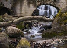 水流量通过曲拱和石头 免版税库存照片