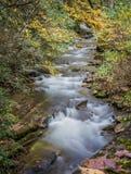 流经山和秋天颜色的小河在10月 免版税库存图片