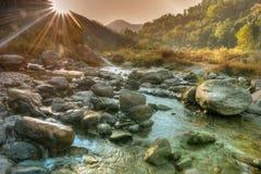 流经岩石的好的河水在黎明 免版税库存图片