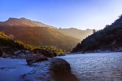 流经自然小瀑布的美丽的河恒河小河平静和平安的自然背景在瑞诗凯诗印度 免版税库存照片