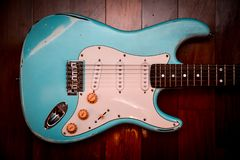 浅兰的电吉他在棕色木背景中 库存照片