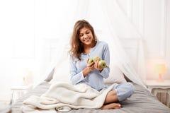 浅兰的睡衣的微笑的深色的女孩在她的手上坐机盖床用绿色苹果在灰色板料 库存照片