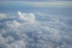 浅兰的颜色天空和经常变动浮动白色云彩天堂视图树荫从飞机窗口的 免版税图库摄影