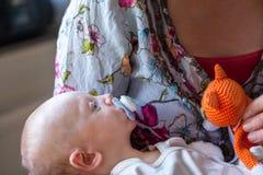 浅景深婴儿男孩孩子的有安慰者的,在他的母亲的谎言用桔子被编织的被充塞的玩具猫武装 免版税库存图片