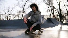 浅灰色的有冠乌鸦的溜冰者坐他的看起来周道的外部的委员会冰鞋公园 太阳强烈发光  股票录像