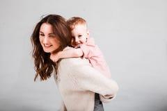 浅灰色的背景的妈妈儿子 免版税库存照片