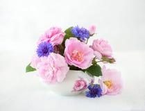 浅粉红色的玫瑰和矢车菊五颜六色的花束在苍白灰色背景 免版税库存照片