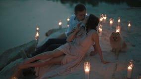 浅粉红色的礼服的迷人的女孩亲吻与英俊的年轻人和接触他的面孔的,当说谎在蜡烛点燃了时 影视素材