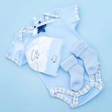 浅蓝色男孩给婴儿穿衣 免版税库存照片