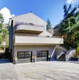 浅褐色的现代房子外部在春天森林里。 免版税库存图片