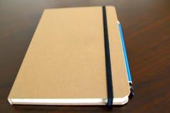 浅褐色的笔记薄书和铅笔 免版税库存照片
