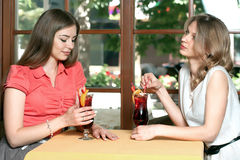浅黑肤色的男人和金发碧眼的女人喝着坐在咖啡馆的果汁饮料 免版税库存照片
