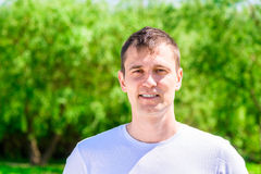 浅黑肤色的男人在一件白色T恤杉的35岁在背景 免版税库存图片