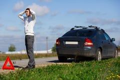 浅黑肤色的男人在残破的汽车附近站立 免版税库存照片