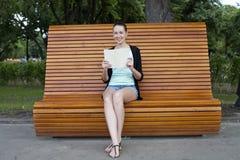 浅黑肤色的男人坐一条长凳在夏天公园 库存照片