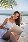 浅黑肤色的男人坐吊床使用微笑对照相机的膝上型计算机 免版税库存照片