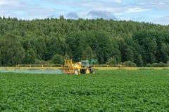 浇灌一个绿色土豆领域的黄色拖拉机 免版税库存照片