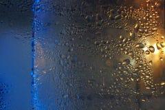 浇灌下落背景露水在冰冷的玻璃的结露纹理 免版税库存图片
