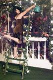 浇灌与蓝色喷壶的妇女玫瑰色花在庭院里 免版税库存图片